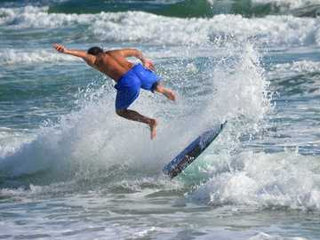 Jumping ocean waves - man in blue shorts surfing on sea waves during daytime. Deerfield Beach, FL, USA
