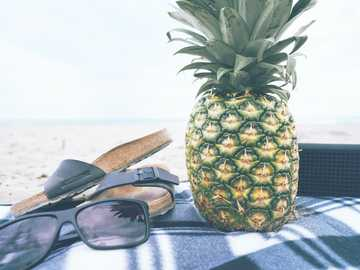 pineapple and accessories - green and yellow pineapple besides black slide slippers and sunglasses. Port Stanley, Canada