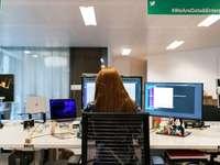 mulher de camisa preta, sentado na cadeira em frente ao computador