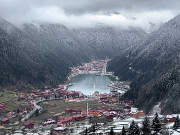 Winter & snow falls - aerial view of city near mountain during daytime. Trabzon, Trabzon, Turkey