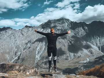 man arms wide open - Jump on Kazbegi mountain. გერგეტის სამება, Georgia