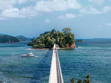 Puente Samaná - biała łódź na morzu w pobliżu zielonych drzew pod białymi chmurami i niebieskim niebem w ciąg