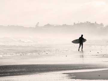 Surfer zmierzający w mgłę - sylwetka osoby chodzącej na piaszczystej plaży trzymając deskę surfingową. Kapsztad, Republika