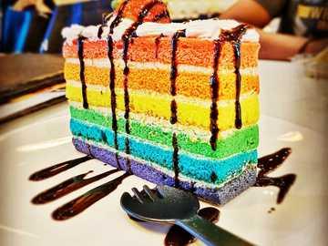 Tęczowy tort zrobiony przy użyciu vivo v15 - wielobarwne ciasto na białym talerzu ceramicznym.