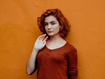 Isis Boell - Frau im roten Hemd mit Knöpfen, das orange Wand lehnt.
