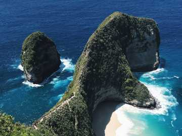 klungkung bali indonesia - green moss on black rock formation near blue sea during daytime. Bali, Indonesia