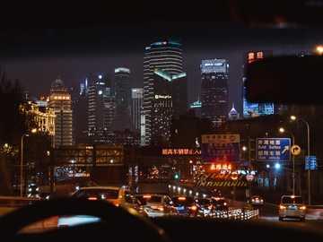 Zbliża się do Bundu z podziwem. - samochody na drodze w pobliżu wysokich budynków w nocy. Szanghai Chiny