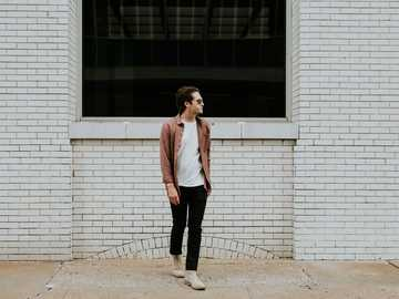 Man in front of brick wall - man standing beside beige brick wall.