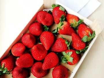 pudełko truskawek - truskawki w białej ceramicznej tacy.