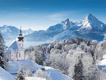 Winter landscape - snow-capped mountains and a small church