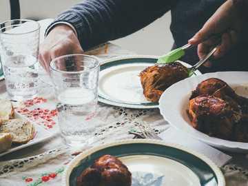 Niedzielna kolacja pieczona - osoba trzymająca gotowane jedzenie szczypcami.