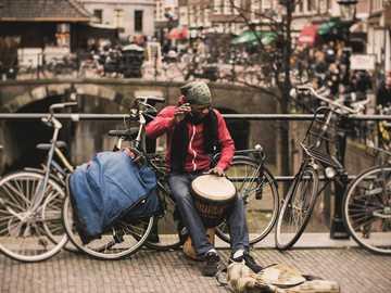 On też był dobry! - mężczyzna w czerwonej koszuli grający na bębnie darbuka, siedząc na szarym rowerze w pobliżu n