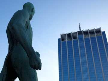 Monumento en frente del edificio - Estatua de hombre desnudo en frente del edificio de gran altura. Bruxelles, Belgique