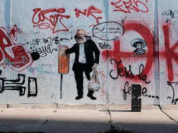 - la photo a été prise directement sur l'appareil photo, sans post-traitement - homme en veste noire debout à côté du mur avec des graffitis pendant la journée. Berlin, Allemag