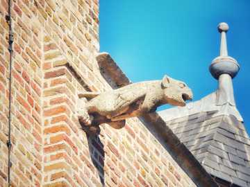 Gargoyle at Belfort Sluis - white animal statue on brown brick wall. Sluis, Niederlande