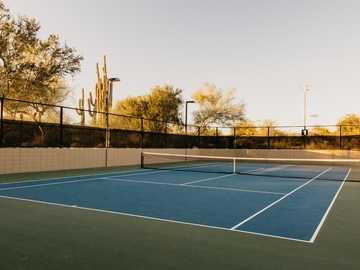 cancha de tenis azul - Cancha de tenis vacía bañada por la puesta de sol del desierto.