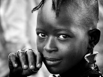 A young girl from the Hamar tribe in the Omo valley region of Ethiopia - toddler with earrings putting her hand on her face in selective focus greyscale portrait photography