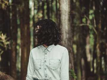 Woman in a shirt in woods - woman in white denim dress shirt taking a photo.