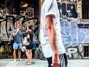 Straßen von Katalonien - Mann, der auf Straße mit Mann und Frau geht, die nahe Wand im Hintergrund sprechen. Gotisches Viert