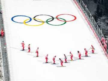 les gens skient pendant les Jeux olympiques d'hiver - un jour, semez de manière excentrique le groupe de volontaires, qui prenait soin de la manche du sa