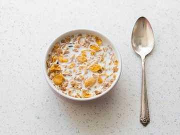 tazón de cerámica blanca con sopa - Un plato de copos de maíz y leche. pavo