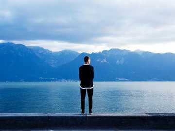 Soledad sobre el lago - Persona con pantalones negros y top de pie en la pared.