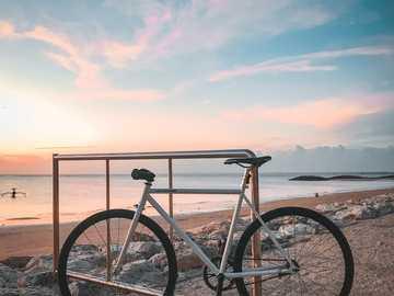 idealny garnitur, skierowany w stronę złotego kąta - czarny rower podmiejski na brązowym piasku w ciągu dnia. Pantai Kelan, Tuban, Badung Regency, Bali
