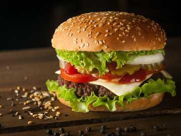 Burger de viande et de fromage entouré de graines de sésame - gros burger sur une table en bois avec du poivre et du sésame.