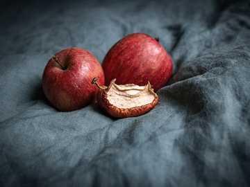 rote Apfelfrucht auf grauem Textil - Drei Äpfel, einer davon alt und trocken.