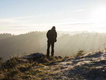 Creux du Van - uomo in piedi sulla scogliera vicino agli alberi durante il giorno.