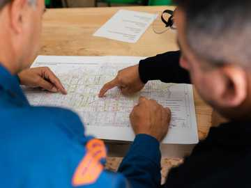 person writing on white paper - Structural engineers assess evacuation and disaster relief map.