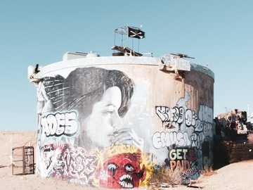 graffiti art on wall during daytime - Abandoned water tank with graffiti and art in Slab City. Slab City, CA, USA