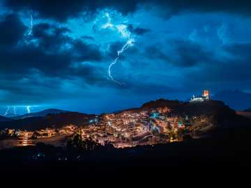 cefalà diana among the flashes - the town of cefalà diana with its castle high in the night surrounded by lightning
