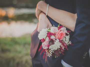 Wedding Day Hug - woman holding flower bouquet while hugging man. Bujenka, Poland