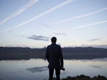 Photographer and lake - man in black top under cloudy sky.