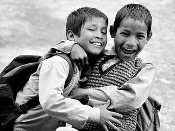 Fotografía en escala de grises de dos niños abrazados mientras se reían - Trekking en los rangos del Himalaya, una vez que nos encontramos con la región de Grahan, que tiene