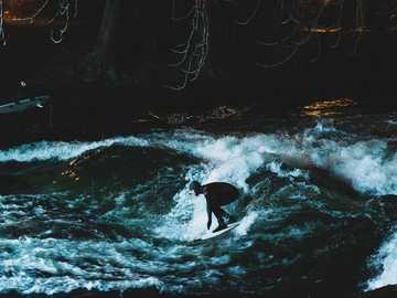Urban surfing in Munich - person surfing on water waves during daytime. Munich, Germany