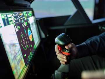 Simulatore di volo volante volante - persona che tiene attrezzo a mano nero e rosso.