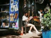 Etwas. - Frau liest Buch, das auf Bank sitzt.
