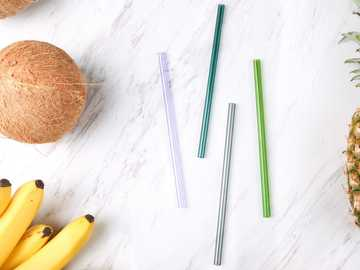 Glass Straw 4 - four assorted-color straws beside coconut, bananas, and pineapple.