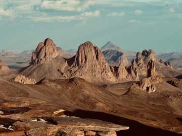 Montagne rocheuse brune sous des nuages blancs pendant la journée - Vue depuis Assekrem (2750m), Sahara Parc national d'Ahaggar - Algérie  fabriqué par rouichi /