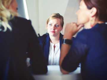 Three businesswomen - three women sitting beside table.