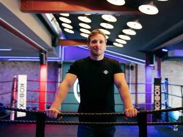 Ingeniero masculino se encuentra en el ring de boxeo - Hombre en camiseta negra con cuello redondo de pie y sonriente.