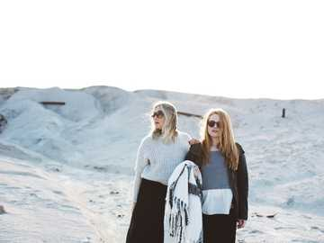 Mom and daughter on the sand dunes - two women standing on snow covered surface. Joplin, United States