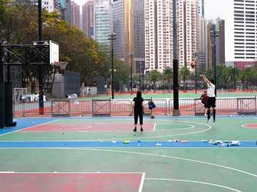 06:44 - Wczesny kosz w Victoria Park - ludzie grający w koszykówkę na boisku do koszykówki w ciągu dnia. Causeway Bay, Hongkong