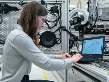 Une ingénieure en électronique effectue des tests de véhicules - femme en chemise à manches longues blanche à l'aide d'un ordinateur portable noir.