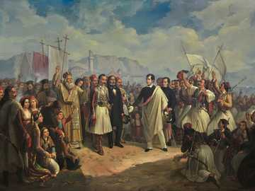 people in traditional dress standing on brown sand during daytime - The Reception of Lord Byron at Missolonghi.