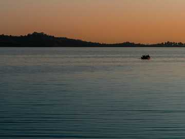 Where sunsets meet the oceans. - silhouette of person riding boat on sea during sunset. Islamabad, Pakistan