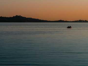 Gdzie zachody słońca spotykają się z oceanami. - sylwetka osoby jadącej łodzią na morzu podczas zachodu słońca. Islamabad, Pakistan