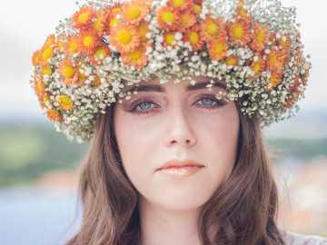 Imponująca korona kwiatowa - kobieta z pomarańczowym i białym nakryciem głowy kwiatu.